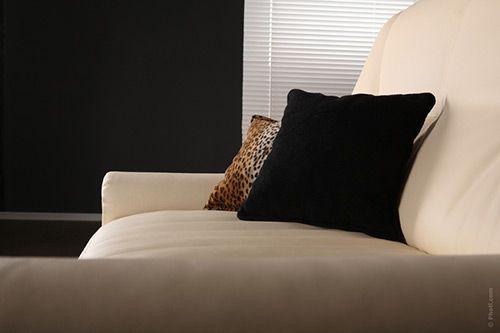 sofá con cojines en negro y leopardo sobre sofá beige