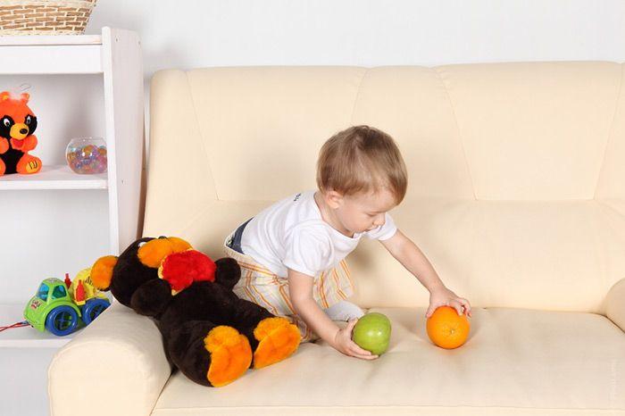 sofa beige con niño jugando